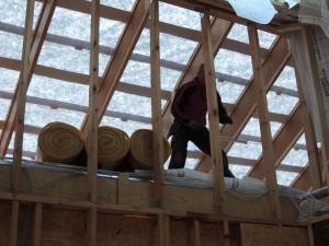 Her er tømrerne igang med at lægge isolering på loftet.