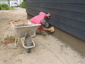 Her er mureren i gang med at pudse soklen på huset.